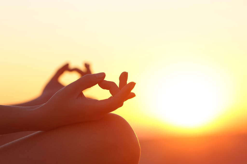 Woman hands exercising yoga at sunset